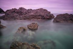 Vågor av havet, himlen och stenarna, stenblock längs kustlinjen Arkivfoto
