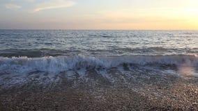 Vågor av havet surfar på stranden på solnedgången stock video
