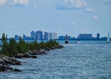 Vågor av Lake Michigan vatten kraschar mot avbrott av väggen, som fartyg reser förbi med horisont av Chicago bakom arkivfoto