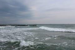 Vågor bryter ut runt om en pir Royaltyfri Bild