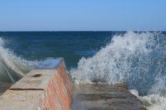 Vågor en vågbrytare Fotografering för Bildbyråer