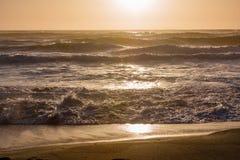 Vågor för solnedgångstrandvatten Royaltyfria Bilder