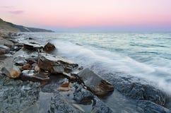 Vågor för stenig strand och havsunder solnedgånghimlen Arkivfoton