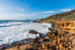 Vågor förbi Alghero den steniga kusten Arkivbild