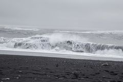 Vågor i den härliga vulkaniska svarta sanden sätter på land Royaltyfri Foto