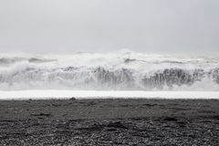 Vågor i den härliga vulkaniska svarta sanden sätter på land Arkivbilder