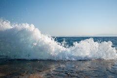 Vågor klippte igenom pir, vågorna störer med simning som var osäker på stranden, farliga vågor arkivfoto