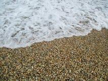 Vågor med lamm och stranden med snäckskal arkivfoton