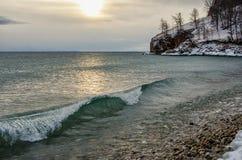 Vågor och färgstänk på Lake Baikal med vaggar, och träd i Uzuri skäller Arkivfoto