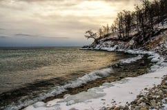 Vågor och färgstänk på Lake Baikal med vaggar, och träd i Uzuri skäller i solnedgång Fotografering för Bildbyråer