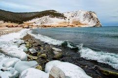 Vågor och färgstänk på Lake Baikal med vaggar och träd nära den Uzuri byn Arkivbilder