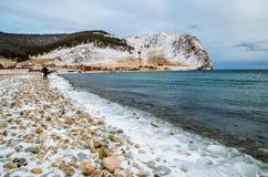 Vågor och färgstänk på Lake Baikal med vaggar och träd nära den Uzuri byn Royaltyfria Foton