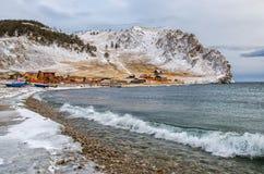 Vågor och färgstänk på Lake Baikal med vaggar och träd nära den Uzuri byn Royaltyfri Foto