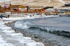 Vågor och färgstänk på Lake Baikal med vaggar och träd nära den Uzuri byn Arkivfoton