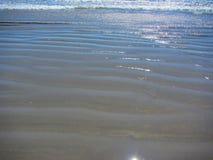 Vågor och krusningsrullning som är inne vid kusten längs en sandig strand Arkivbilder