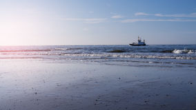 Vågor och skepp på stranden Arkivfoto