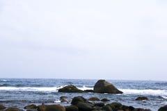 Vågor och stenar under Sanya, Kina Arkivfoto