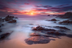 Vågor och vaggar i rörelsesuddighet på kustlinjen på gryning Royaltyfria Bilder