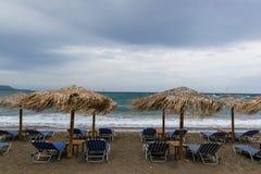 Vågor och vind på stranden med paraplyer och sunbeds royaltyfria foton