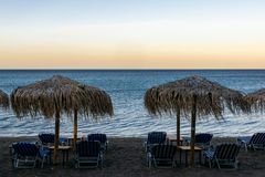 V?gor och vind p? stranden med paraplyer och sunbeds, vardagsrumstolar p? solnedg?ng arkivbilder