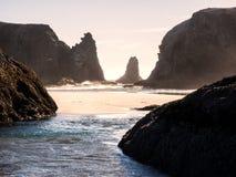 Vågor på den sandiga stranden med vaggar buntar Arkivfoto