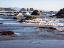 Vågor på den sandiga stranden med vaggar buntar Royaltyfri Bild