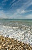 Vågor på ett Pebble Beach Royaltyfria Bilder