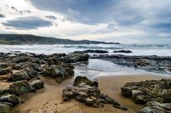 Vågor på kusten i Verdicio sätter på land i Asturias Spanien Det krabba havet i en jungfrulig strand med vaggar och skum på afton arkivbilder
