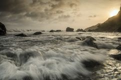 Vågor på menganti sätter på land på solnedgången, kebumen, centrala java Royaltyfria Bilder