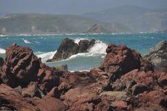 Vågor på rött vaggar sydkustgummistövel Royaltyfri Fotografi