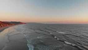 Vågor på stranden i aftonen arkivfilmer