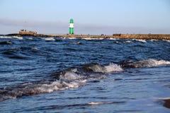 Vågor på stranden med fyren i bakgrund Royaltyfri Fotografi
