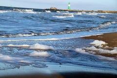 Vågor på stranden med fyren i bakgrunden Royaltyfri Fotografi