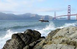 Vågor på stranden vid golden gate bridge royaltyfria foton