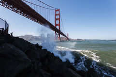 Vågor plaskar upp närliggande på klippor under Golden gate bridge Arkivfoto