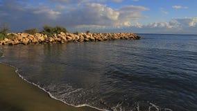 Vågor rullade på en sandig strand och en stenpir lager videofilmer