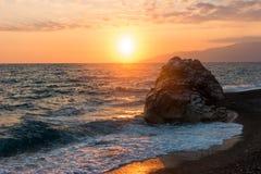 Vågor rullande på linjen för havskusten med enormt vaggar på solnedgången royaltyfri foto