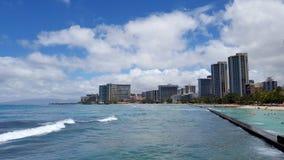 Vågor rullar in i kust, som folket spelar i det skyddade vattnet Arkivbilder