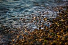 Vågor rullar på små stenar under solnedgång arkivbild