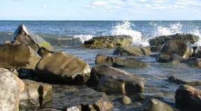 Vågor slår mot stenar, ett buttert landskap Arkivbild
