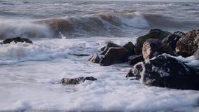 Vågor slår på en klunga av svarta stenar i havet på sanden mot himlen stock video