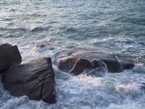 Vågor slår på stenarna med färgstänk royaltyfri foto
