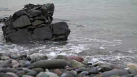 Vågor slår på vaggar vid havet stock video