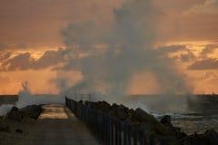 Vågor slogg pir framme av solnedgången på Nr Vorupoer på Nordsjönkusten i Danmark Royaltyfri Bild