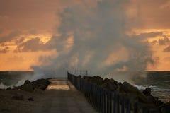 Vågor slogg pir framme av solnedgången på Nr Vorupoer på Nordsjönkusten i Danmark Arkivbilder
