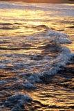 Vågor som är ljusa vid solnedgångavbrottet på den medelhavs- seacoasten arkivfoton