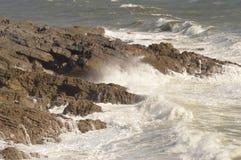 Vågor som över bryter, vaggar mumlar nära, Wales, UK Arkivbild