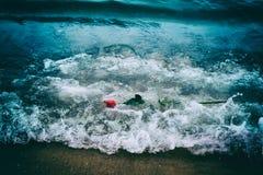 Vågor som bort tvättar en röd ros från stranden Tappning Förälskelse fotografering för bildbyråer
