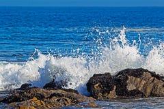 Vågor som bryter över den beströdde musslan, vaggar royaltyfri foto