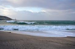 Vågor som bryter mot en strand med solnedgångljus Löst hav med skum La Coruna, Spanien, höststorm arkivbilder
